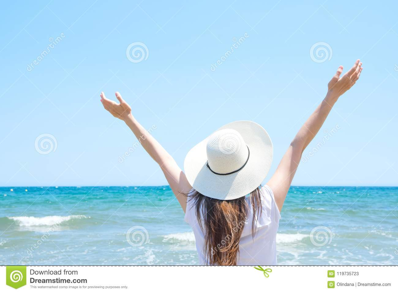 Young Pretty Caucasian Woman with Long Chestnut Hair in Hat Hands Lifted up in the Air Stands at Beach Looks at Turquoise Sea