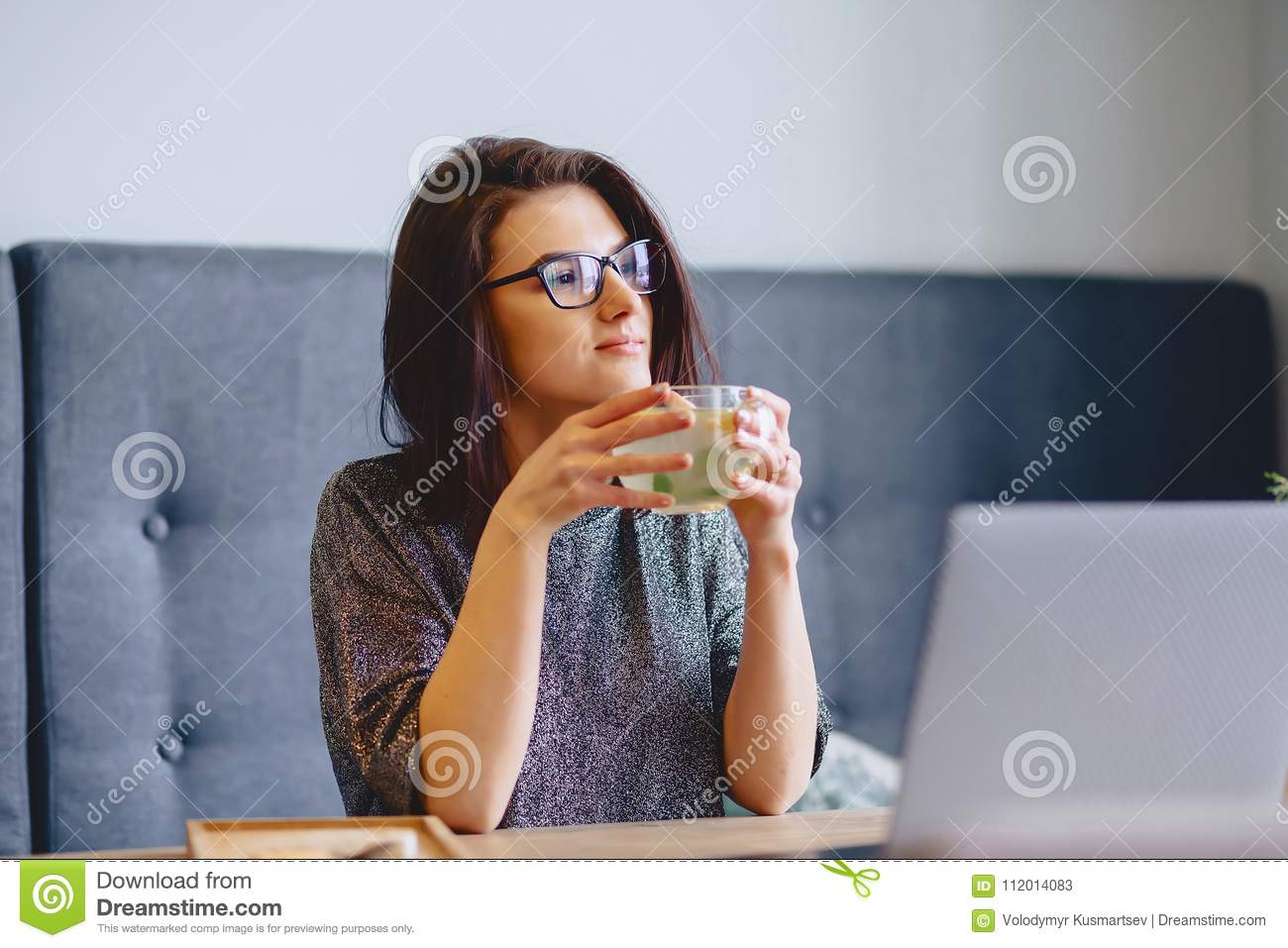 young pretty girl drinking hot tea with lemon for a laptop