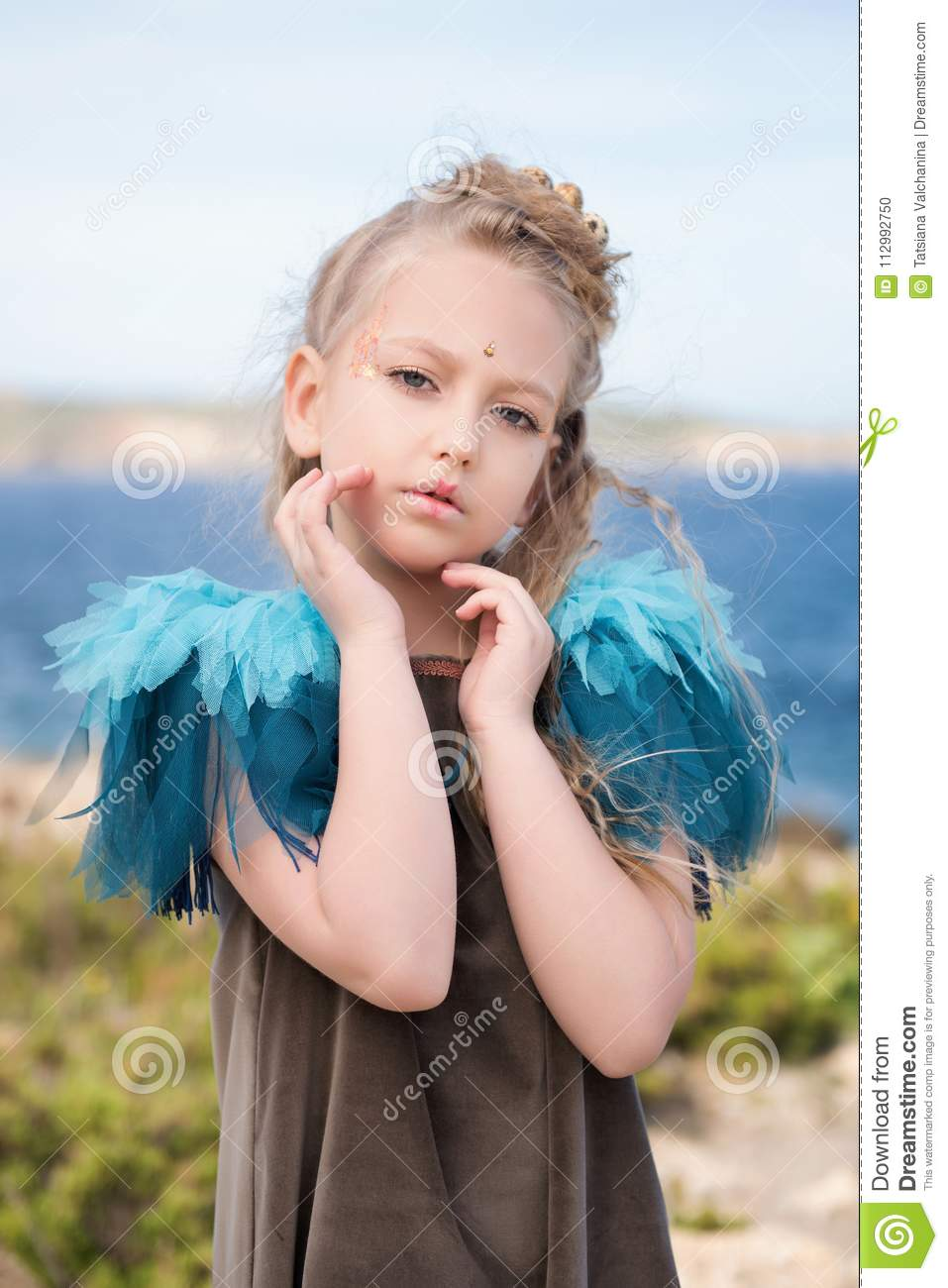 Young pretty girl model posing on the beach with a birdie costume
