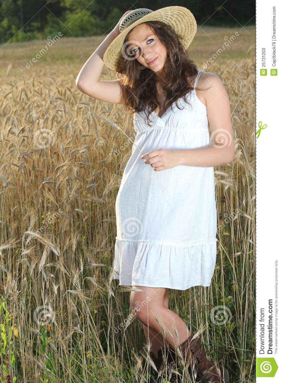 Young pretty girl posing in a wheat field