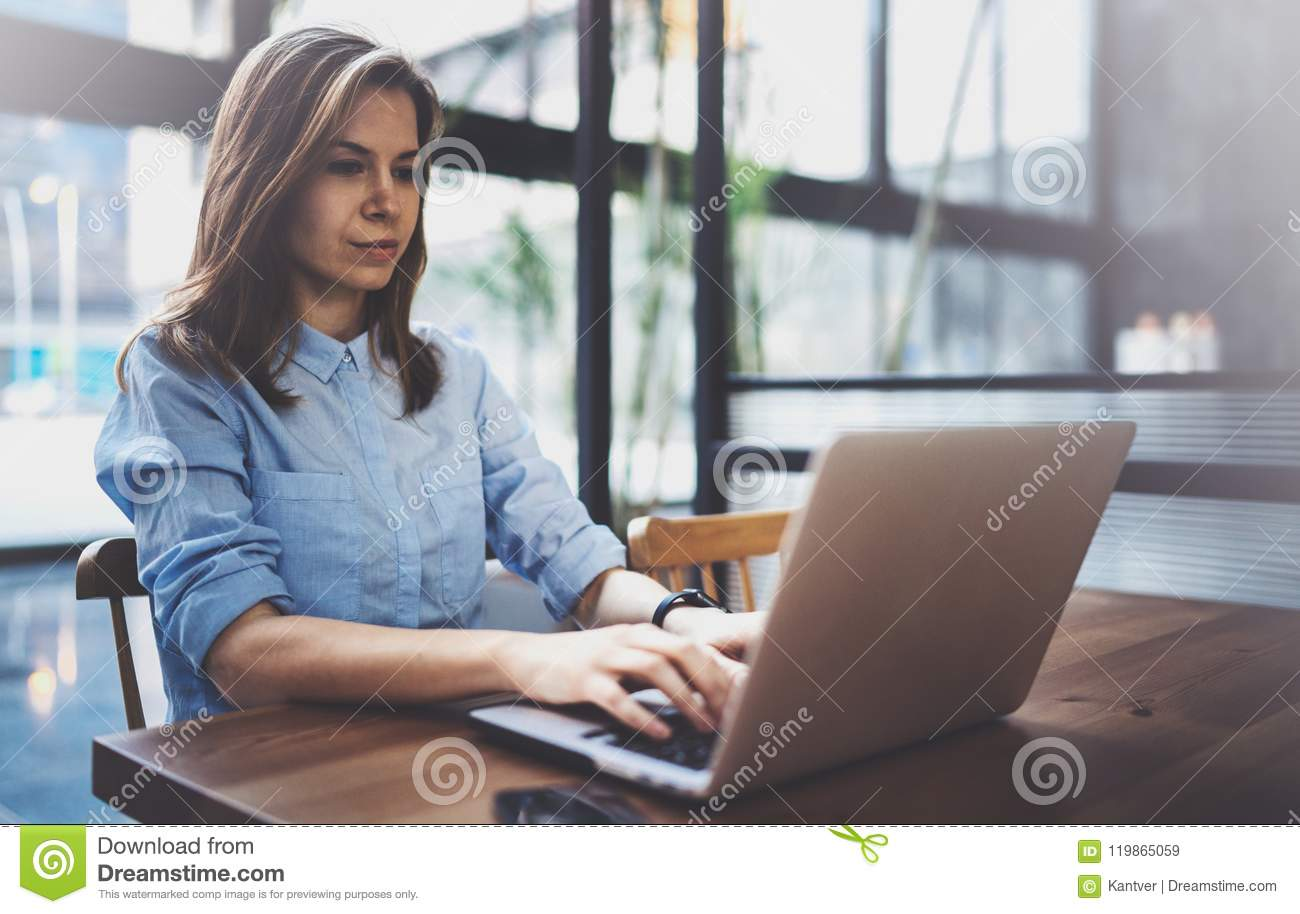 Young pretty girl working on laptop and using mobile smartphone at her workplace at modern office center.Horizontal