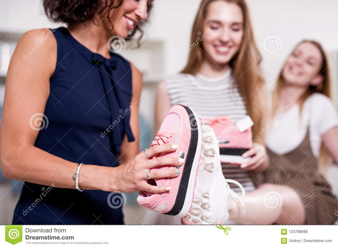 Young pretty lady standing at one leg while her friend checking new footwear size comparing it with old shoes sole