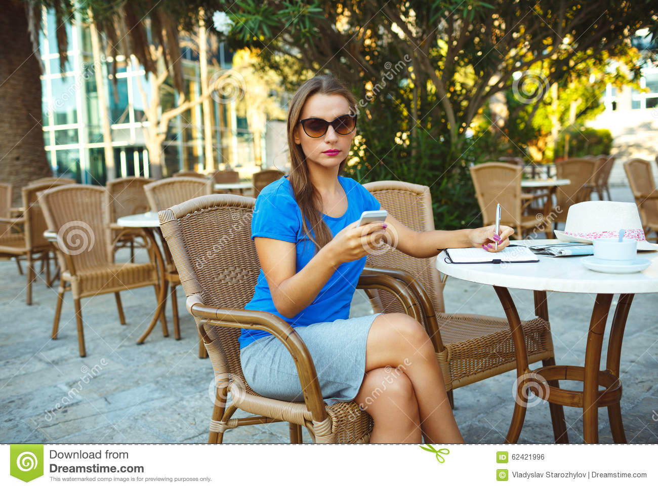 Young pretty modern blogger using smartphone and makes notes in