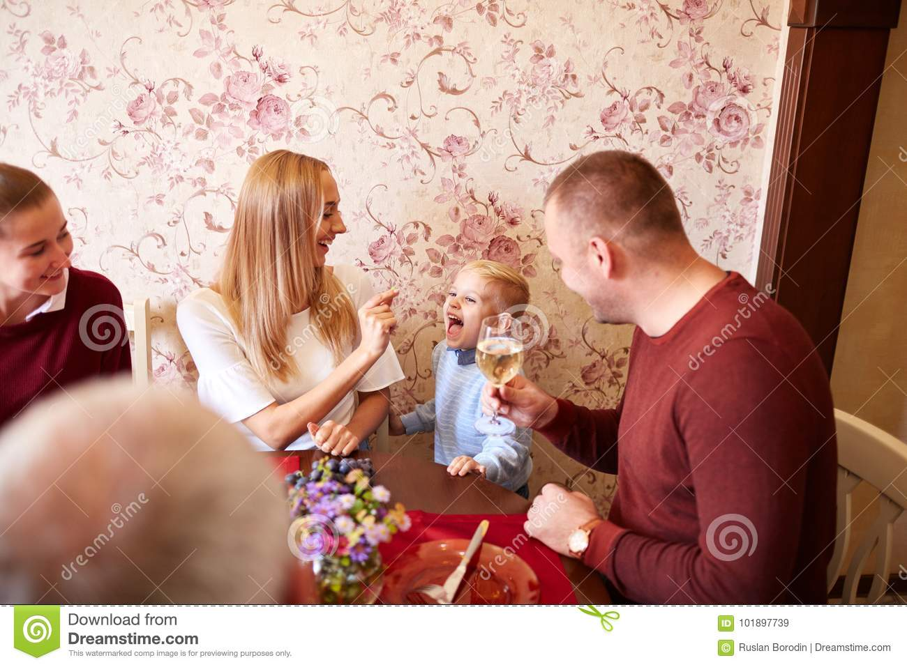 Happy mom and son at the Christmas or Thanksgiving dinner on a festive background. Family bonding concept.