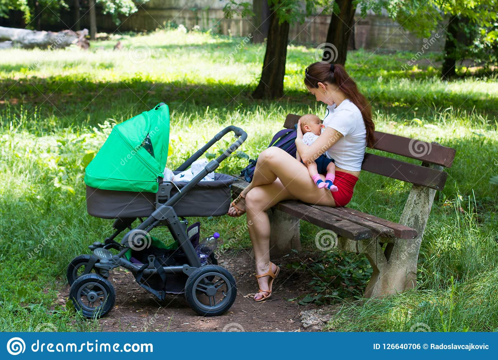 Young mother breast-feeding her cute baby, holding infant gently in hands and sitting on the park bench, next green stroller