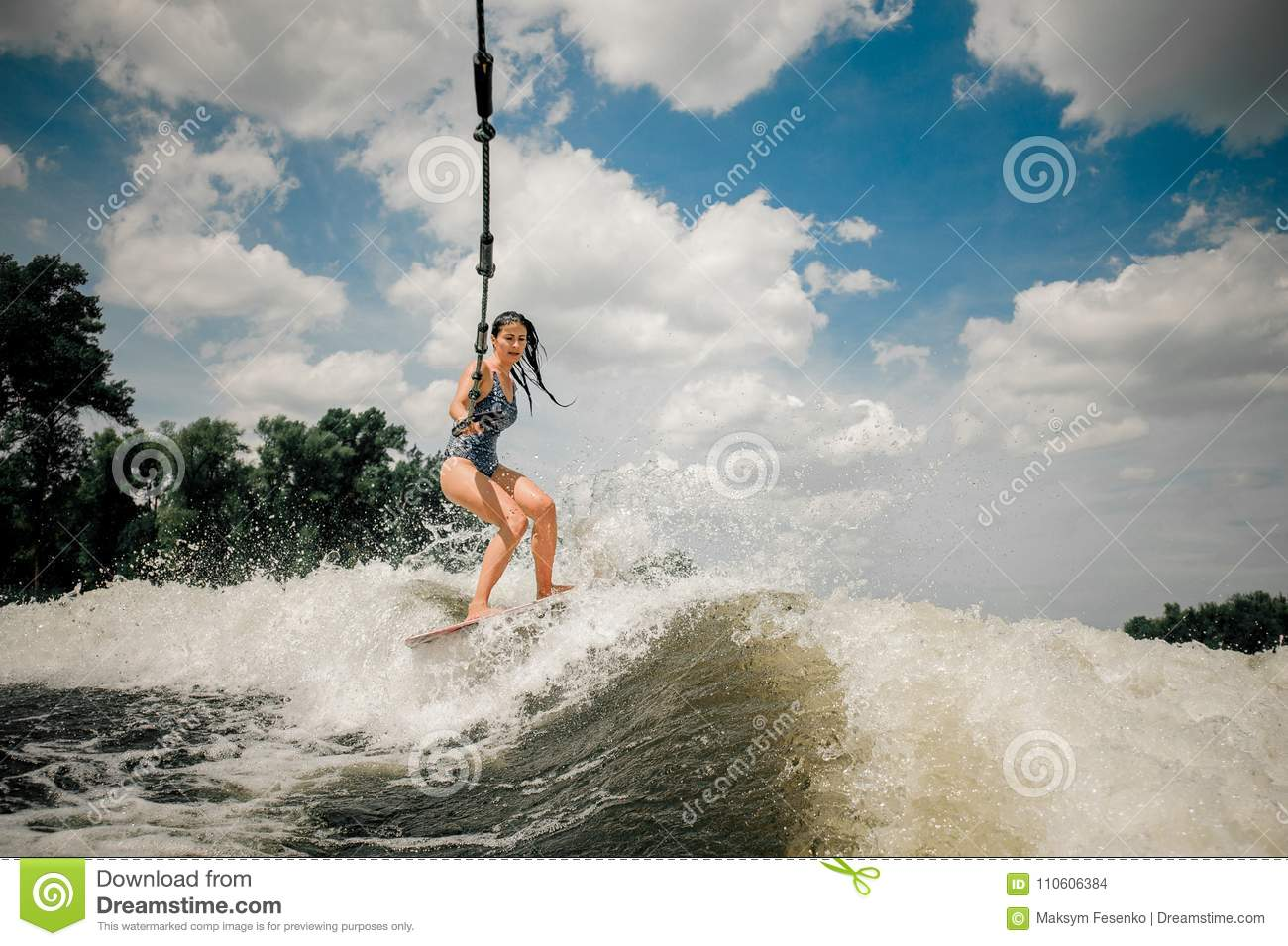 The ladys wakeboard is towed behind a motorboat by rope