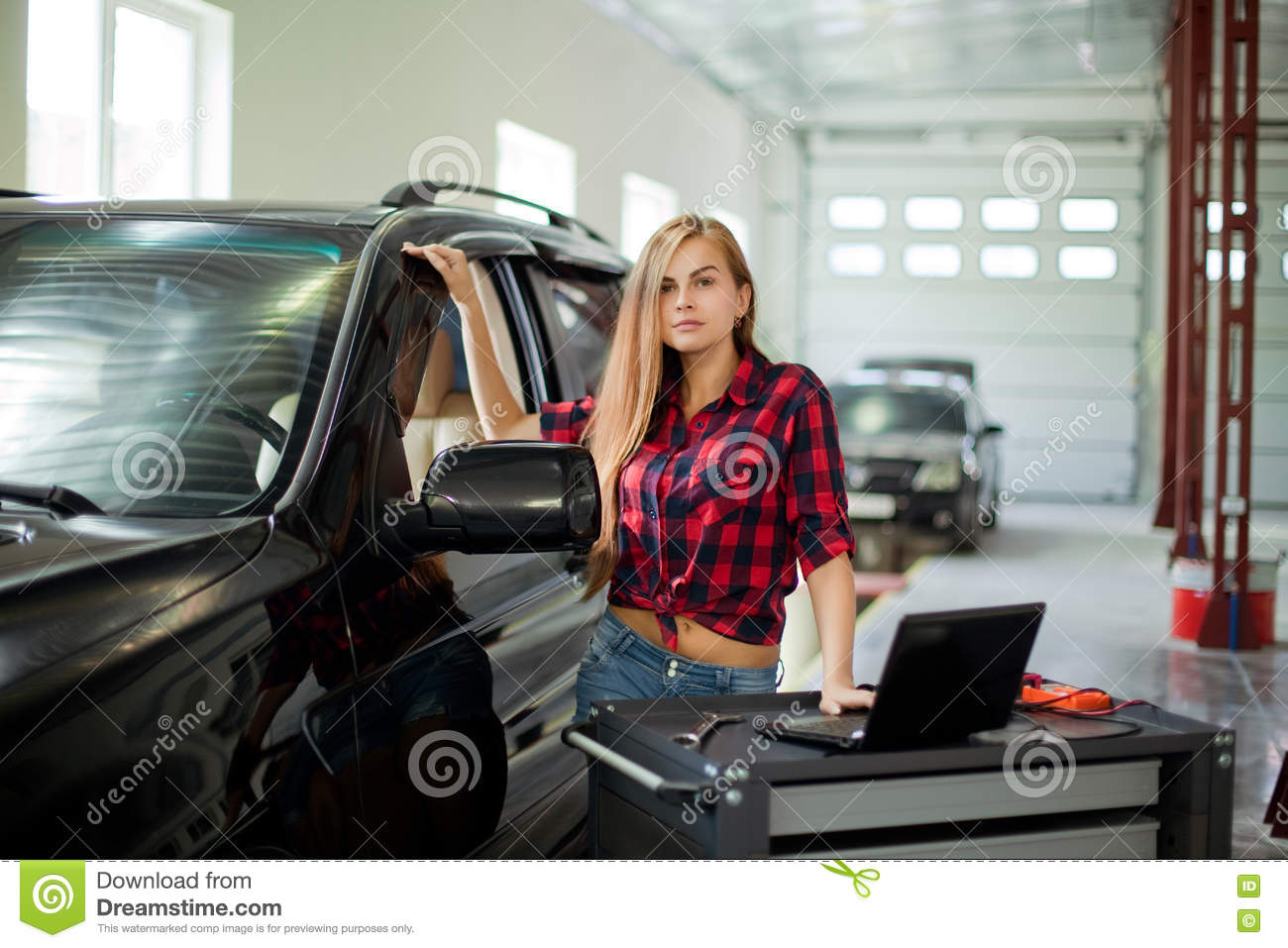 Young pretty woman as a mechanic in checked shirt witch for Garage diagnostic auto
