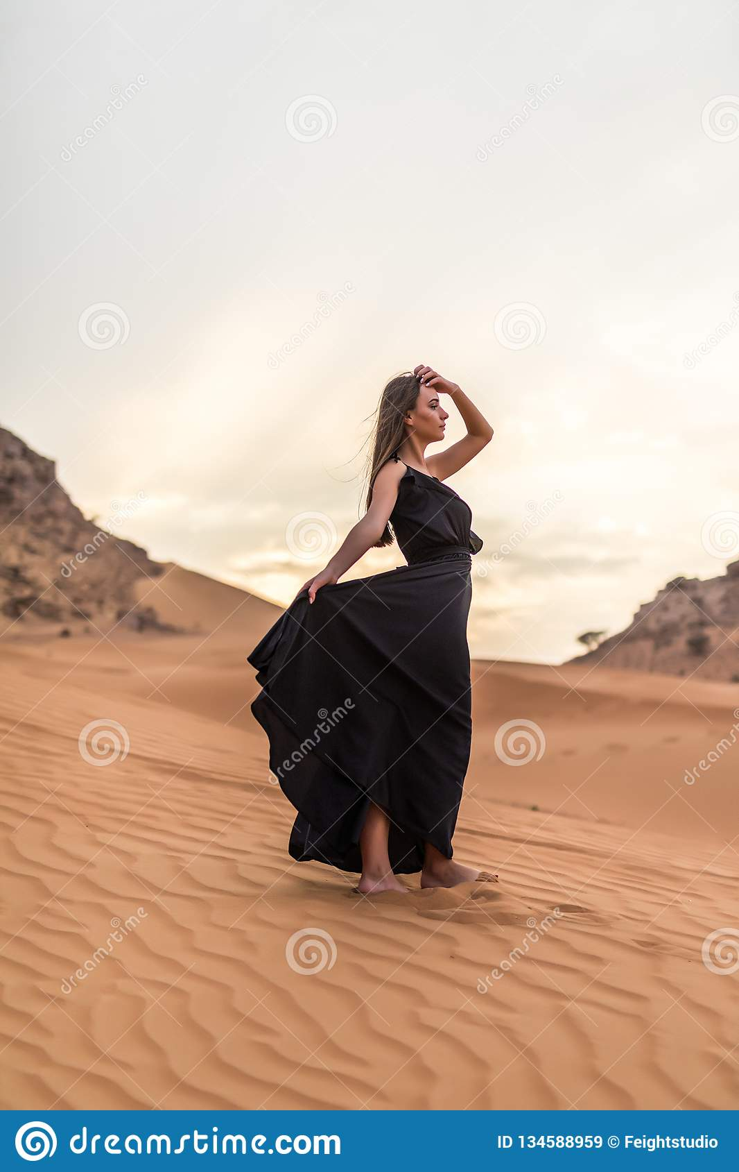 Young pretty woman in black dress stands on dune in desert at sunny hot day