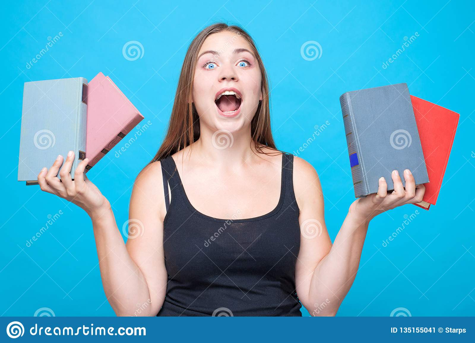 Young pretty woman with 2 books in each hands screams with strong emotions with mouth up.