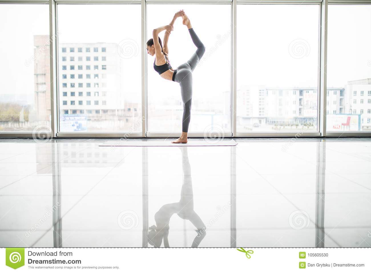 Young pretty woman doing stretching exercise on yoga mat. Fitness, sport, training and lifestyle concept.