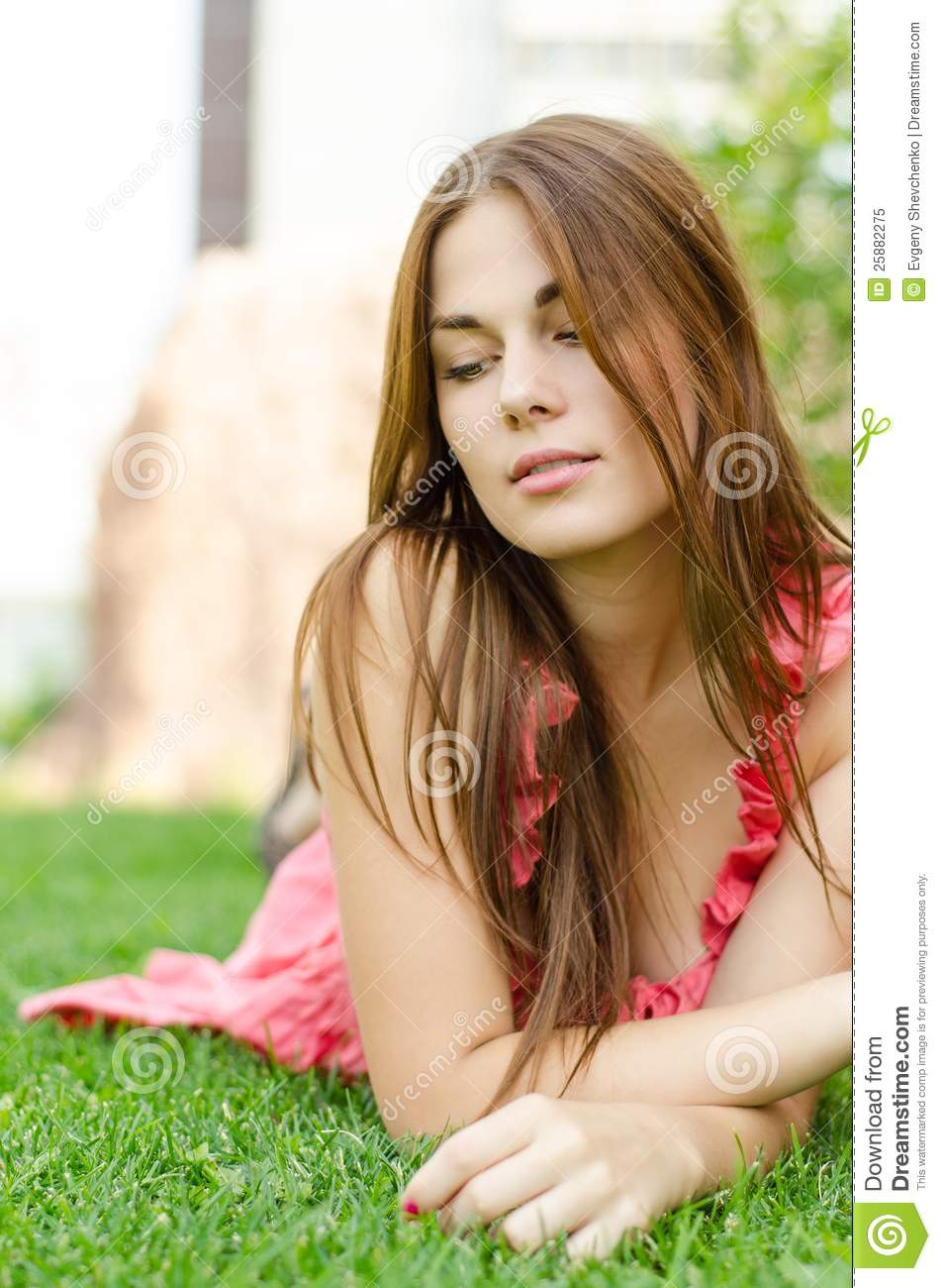 Young Pretty Woman Lying On Green Grass In Park Royalty