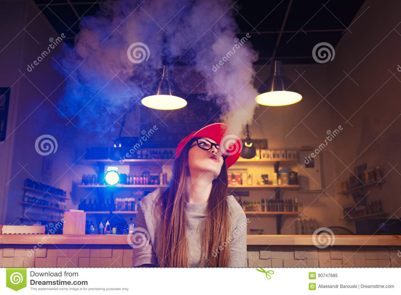 Young Pretty Woman In Red Cap Smoke An Electronic Cigarette