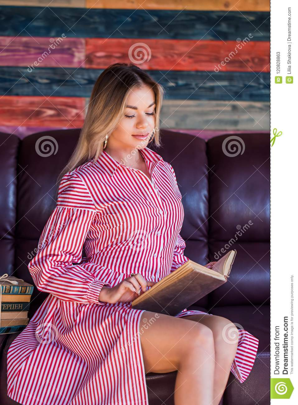 Young pretty woman sitting and reading a book enjoys of rest