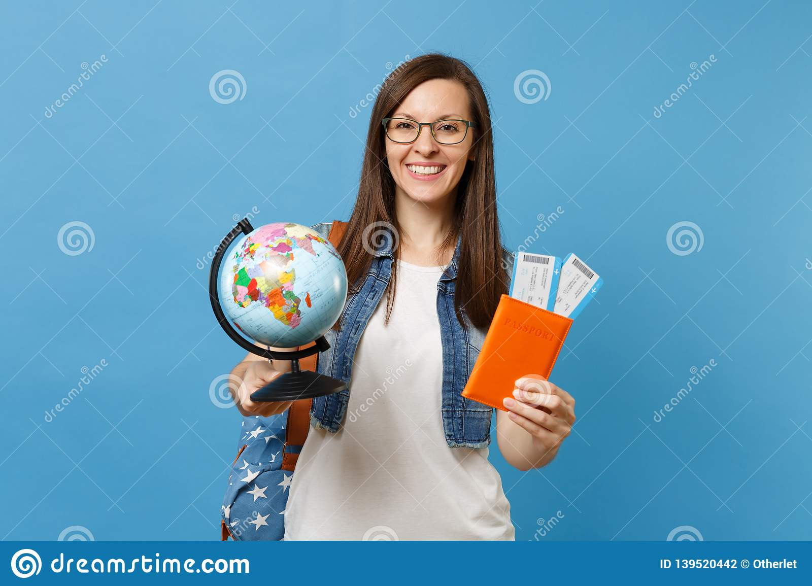 Young pretty woman student in glasses with backpack holding world glove, passport, boarding pass tickets isolated on