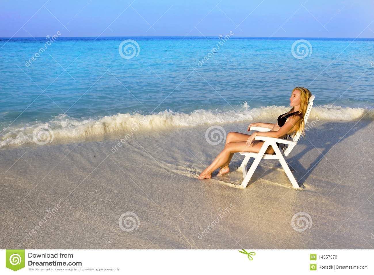 young pretty woman tans in beach chair in ocean stock