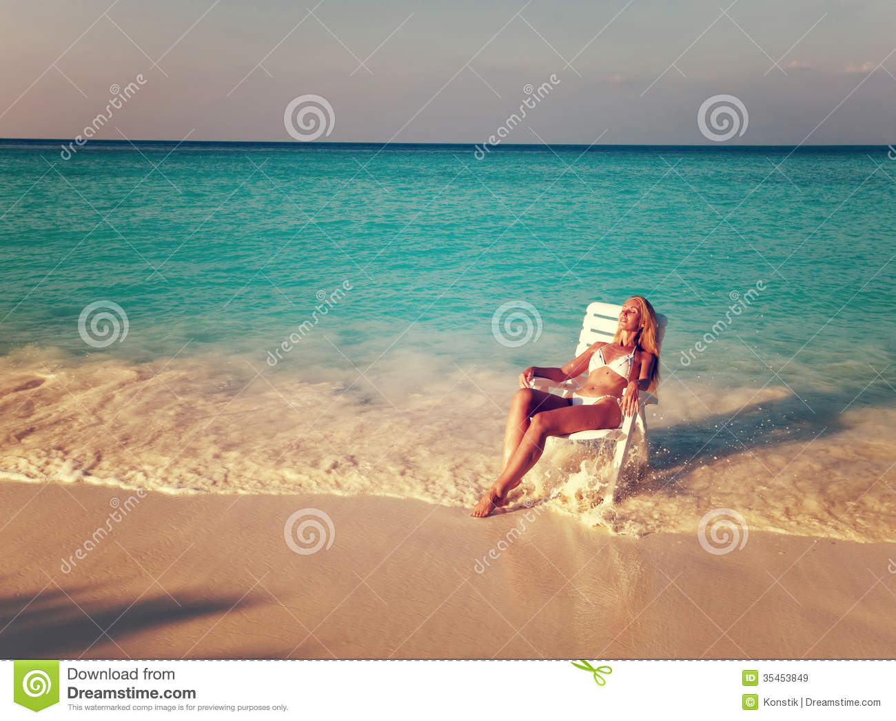 young pretty woman tans in beach chair sea tropical
