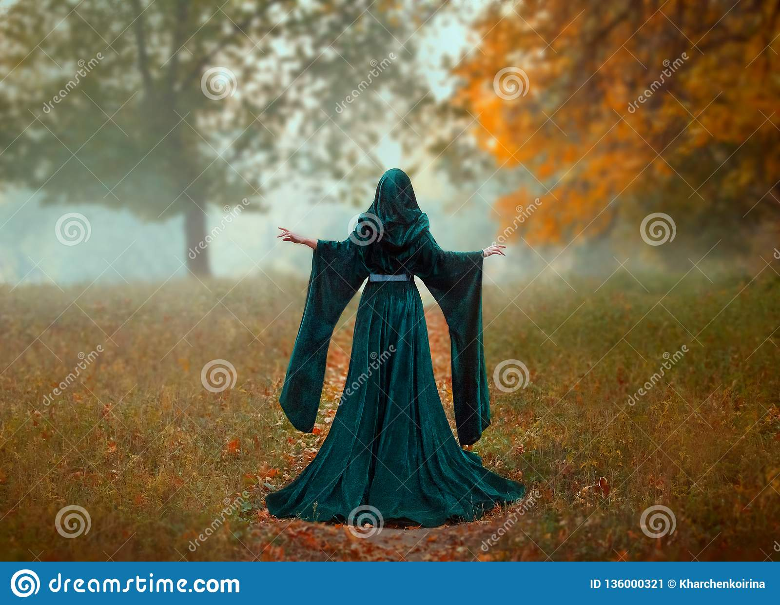 Young priestess holds a secret rite of sacrifice, is alone in the autumn forest on a large glade with fallen orange