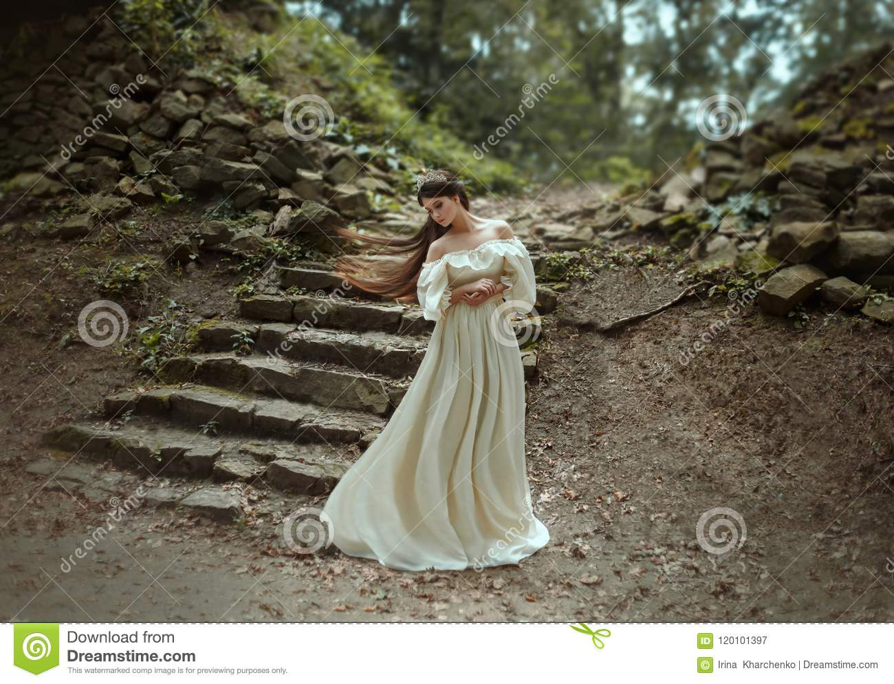 Young princess with very long hair posing against the background of an old stone staircase. The girl has a crystal crown