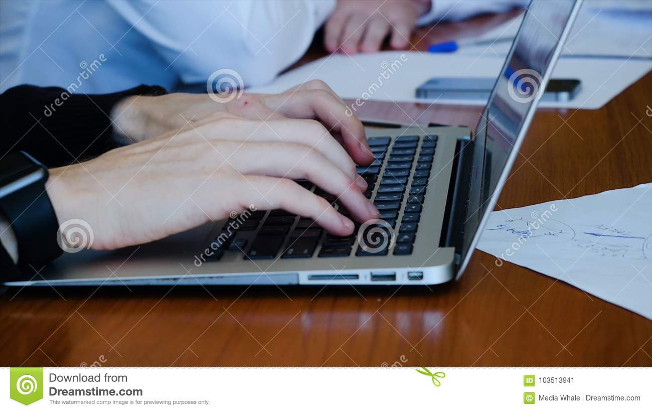 Young professional businessman wearing black turtleneck and using modern laptop, Close-up of male hands typing on