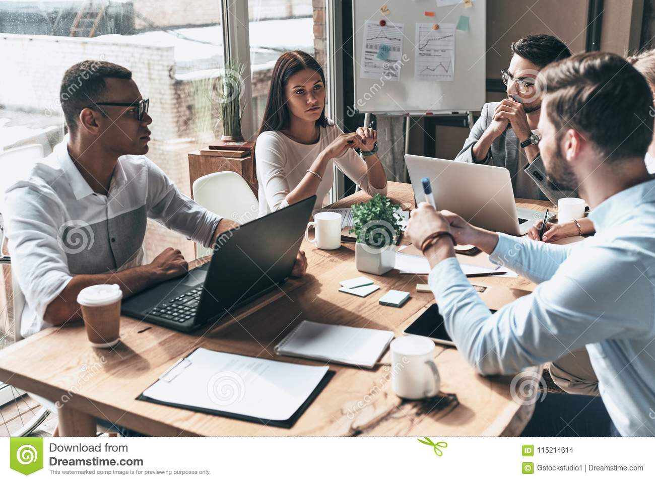 Young professional team. Top view of young modern people in smart casual wear discussing business while working in the creative o