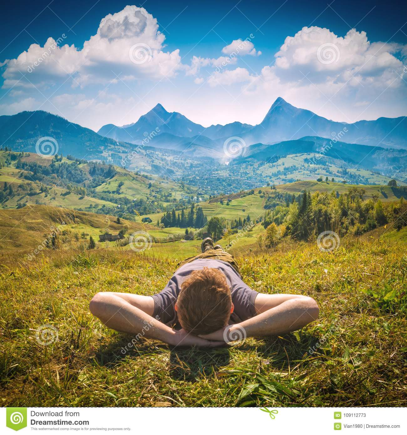 Young red hair man lying on a hill