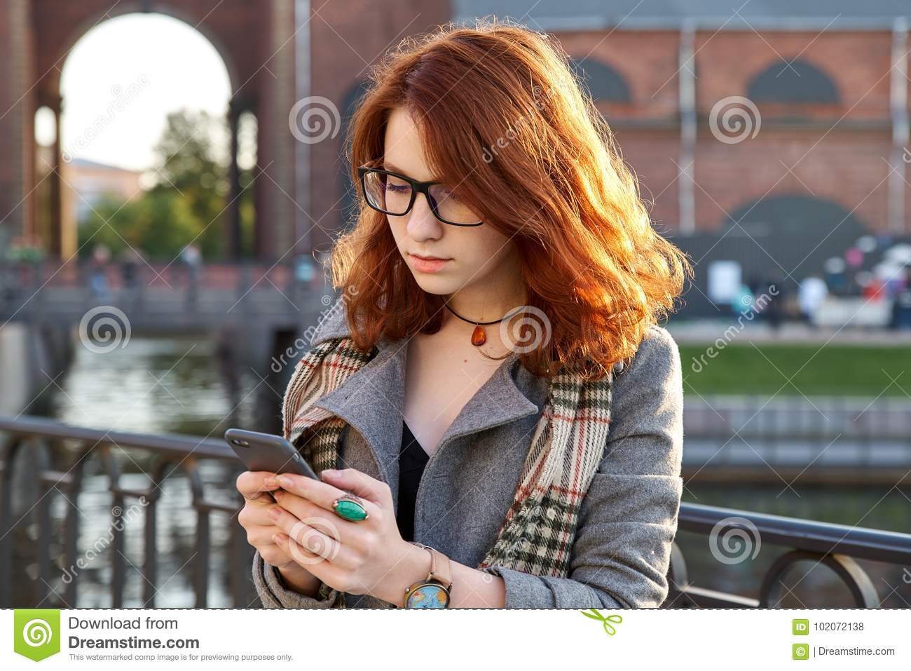 Modern redhead young woman in park in autumn using smart phone. girl with curly ginger hairstyle, texting, smiling, standing outdo