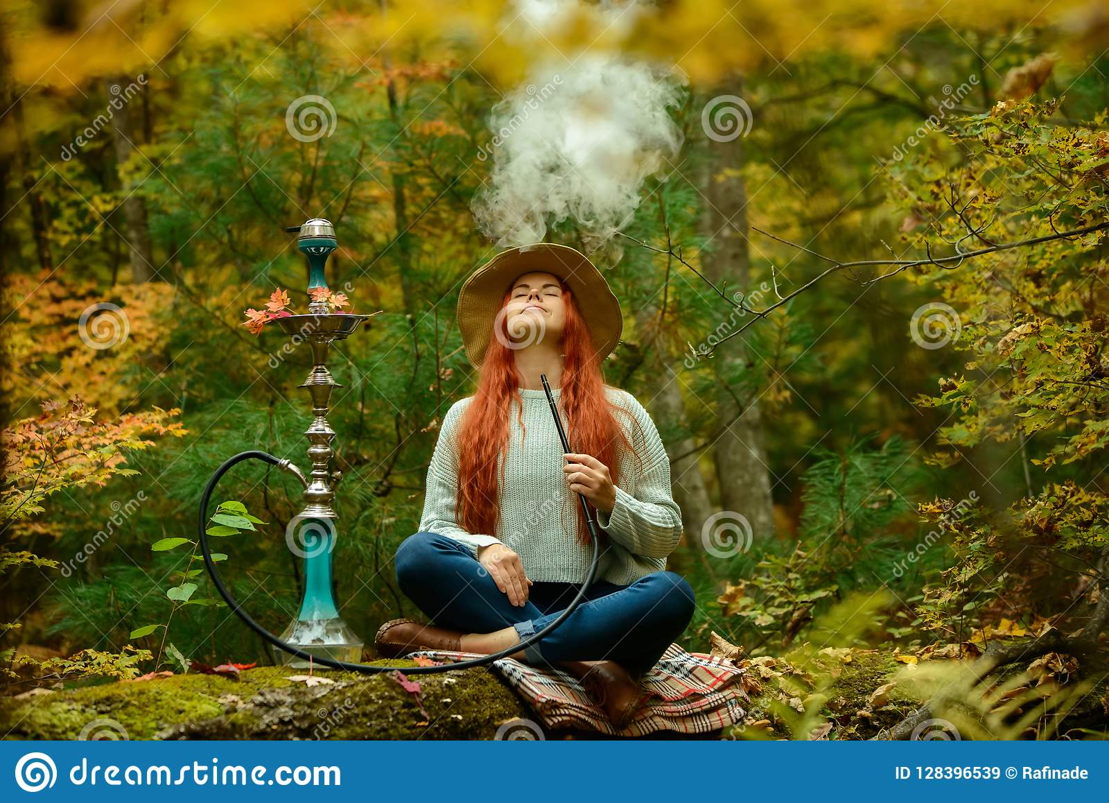 Young redhead woman smoking Hookah in forest