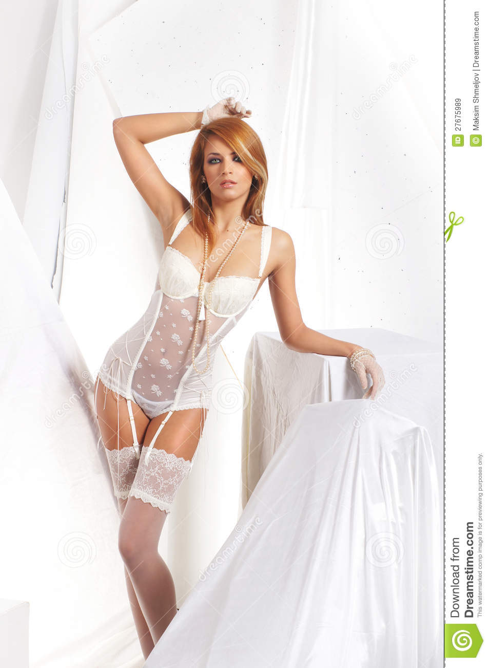 5b0292d9e6f A young and attractive redhead Caucasian woman posing in white erotic  lingerie. The image is taken on a white silk background.