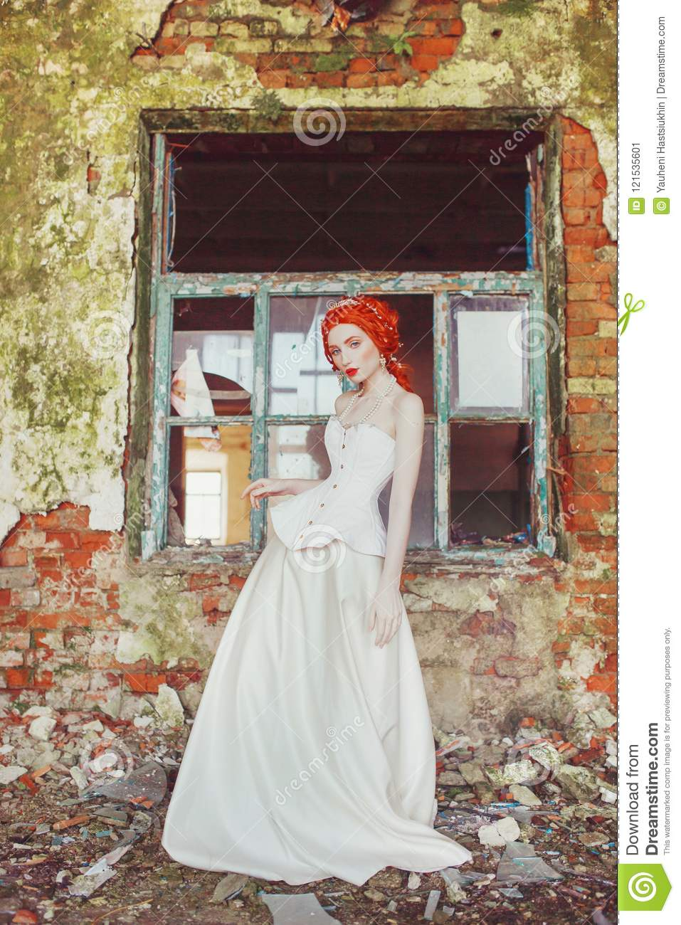 Young renaissance redhead princess in old castle. Fabulous rococo queen in white dress against backdrop of old stone wall.