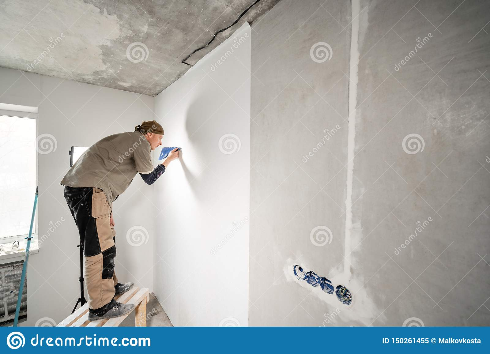 Young repairman aligns with plastic spatula. Worker glueing wallpapers on concrete wall. Repair the apartment. Home