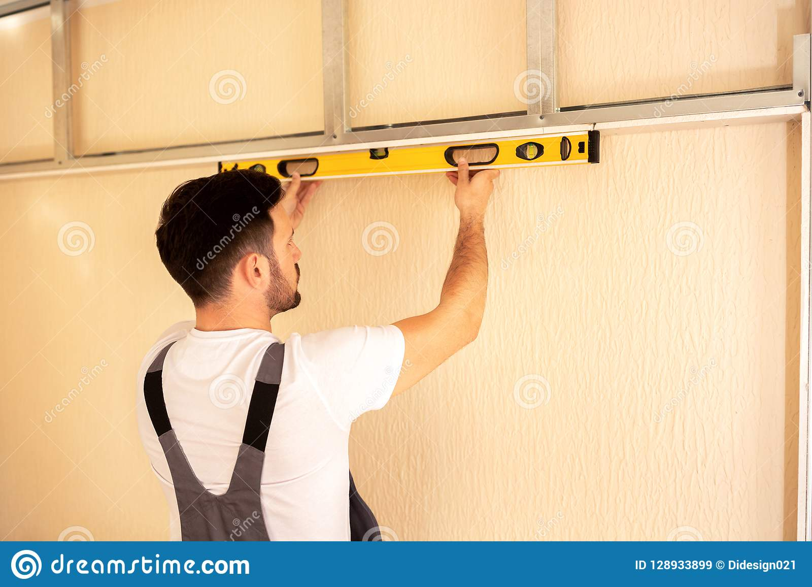 Young repairman checking whether a surface is horizontal