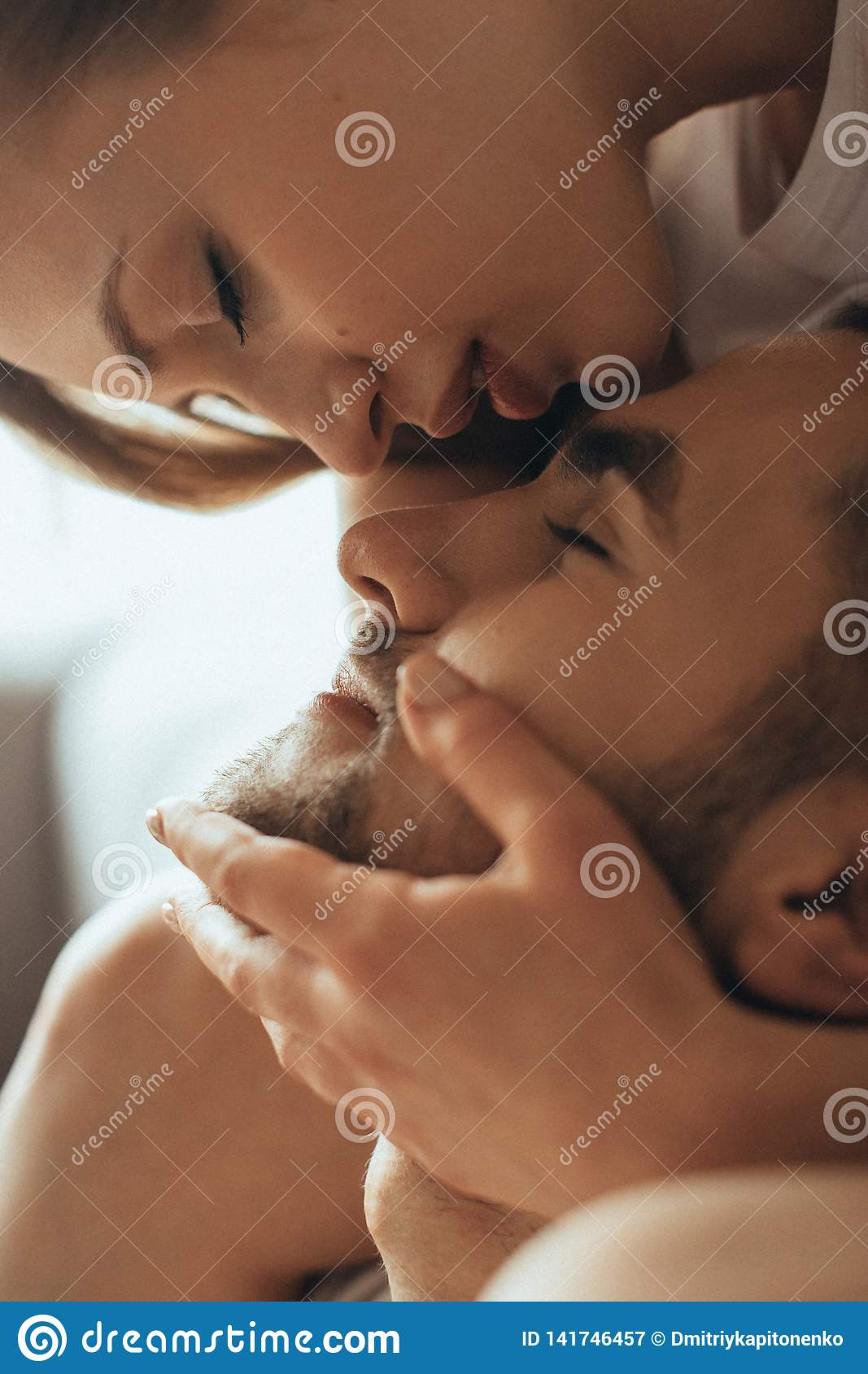 Close-up of young romantic couple is kissing and enjoying the company of each other at home