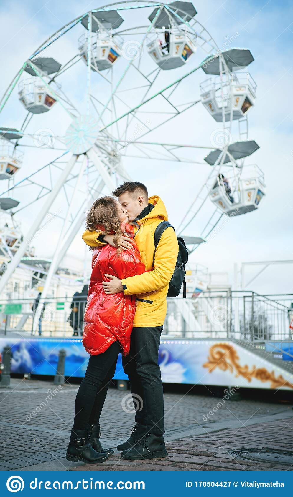 Young Romantic Couple Kissing Hugging Walking On The Street Wearning In Bright Down Jackets Ferris Wheel On Stock Image Image Of Embracing City 170504427