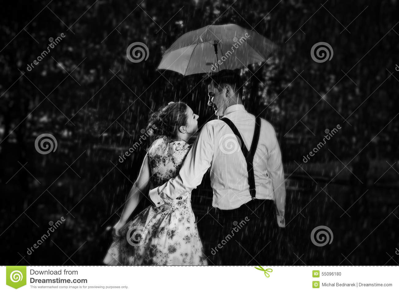 Young romantic couple in love flirting in rain men holding umbrella dating romance black and white