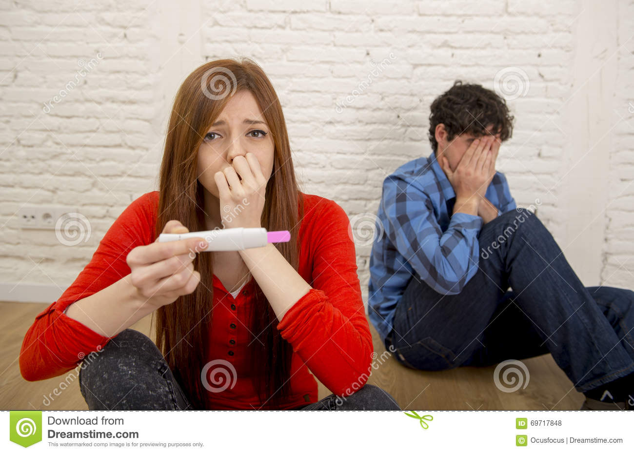 Young sad couple scared in shock and surprise reading pink positive pregnancy test overwhelmed in panic