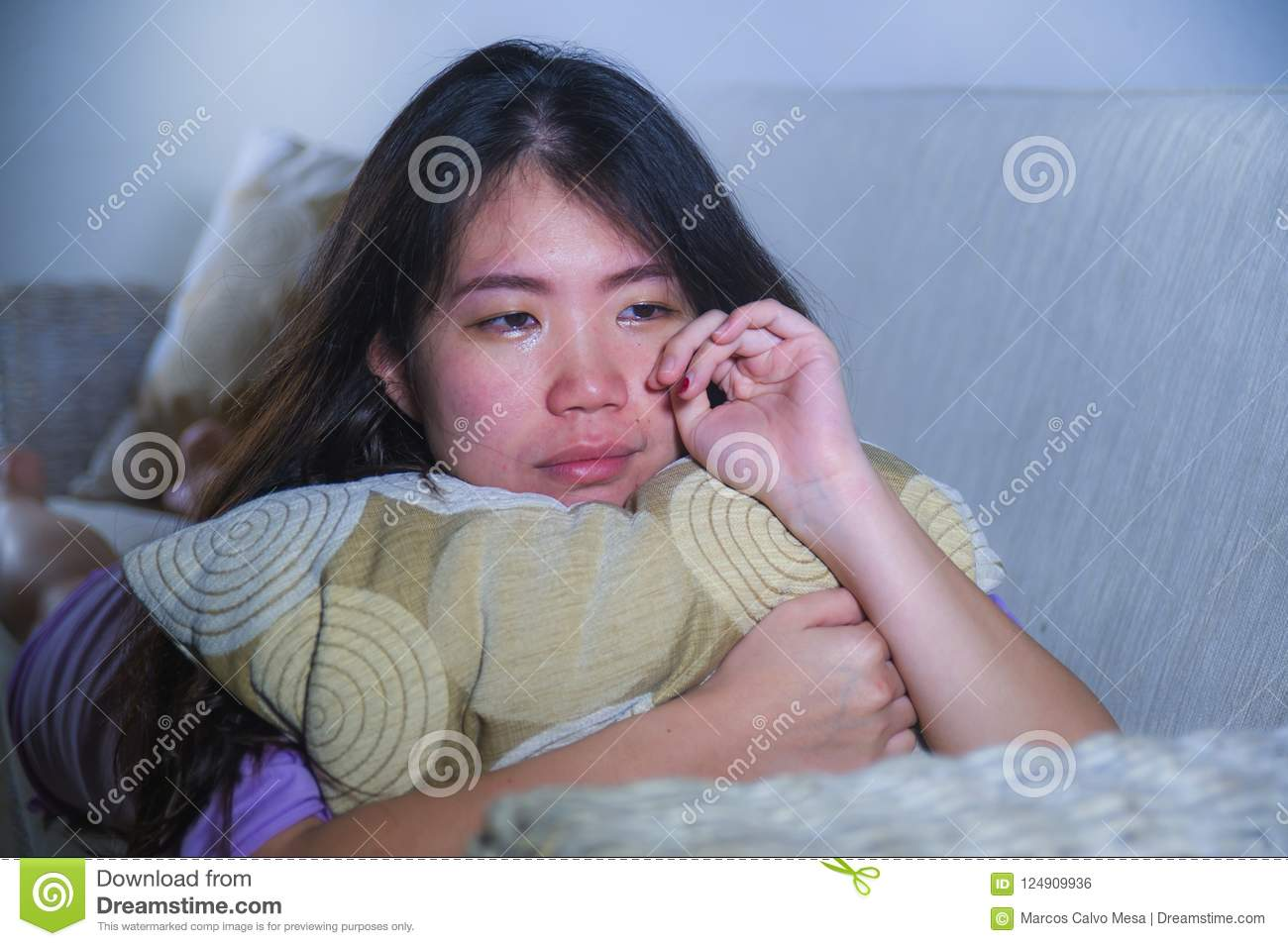 Young sad and depressed Asian Korean woman at home sofa couch crying desperate and helpless suffering anxiety and depression feeli