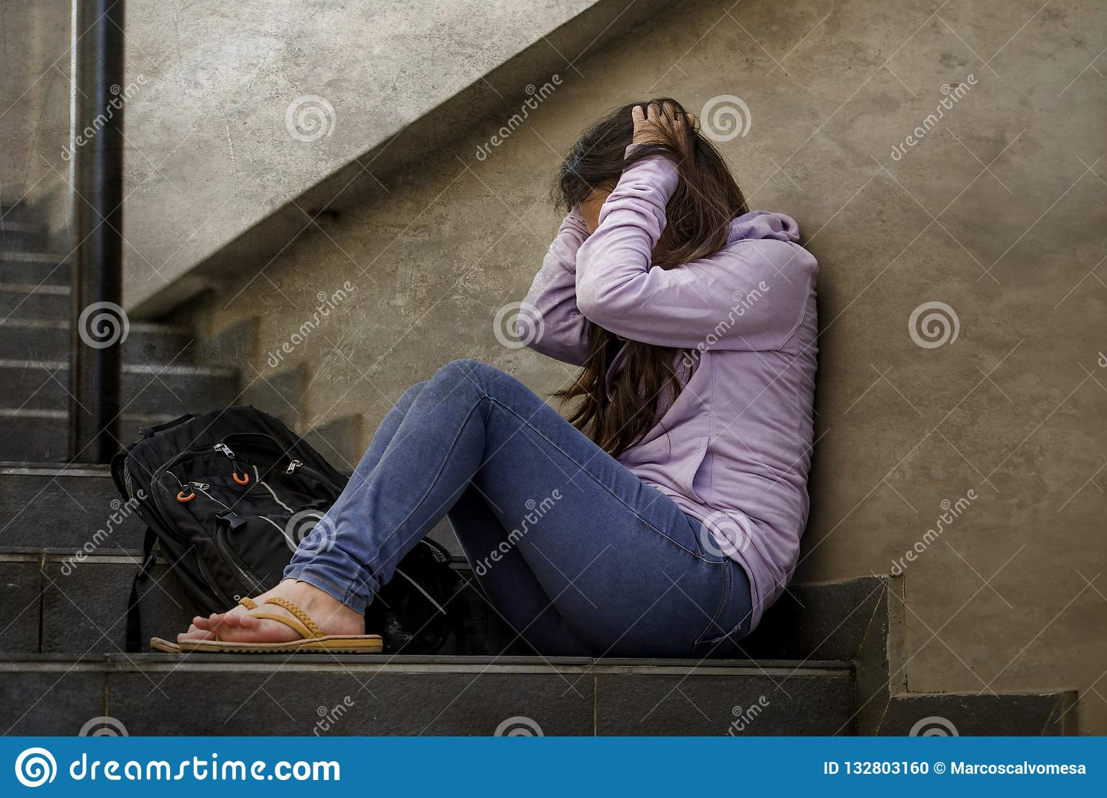 Depressed student woman or bullied teenager girl sitting outdoors on street staircase scared and anxious victim of bullying