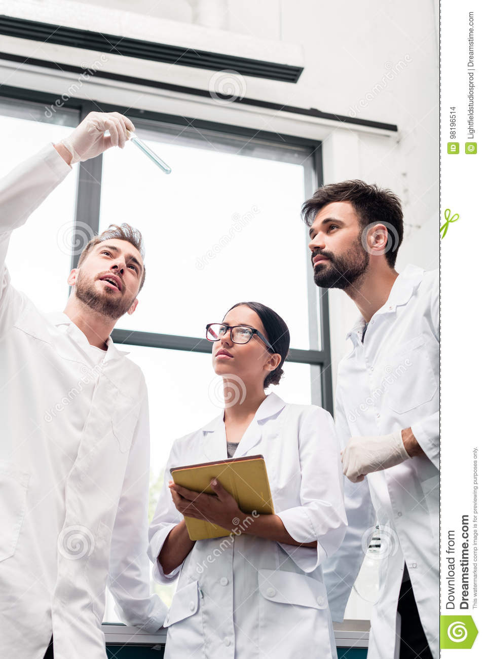 Young scientists in white coats examining test tube and using digital tablet