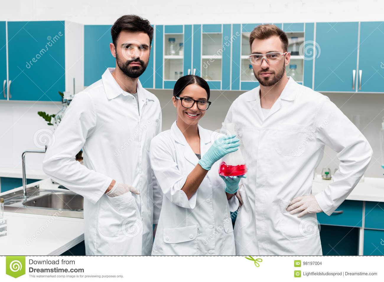 Young scientists in white coats holding flask with reagent and smiling at camera in chemical lab