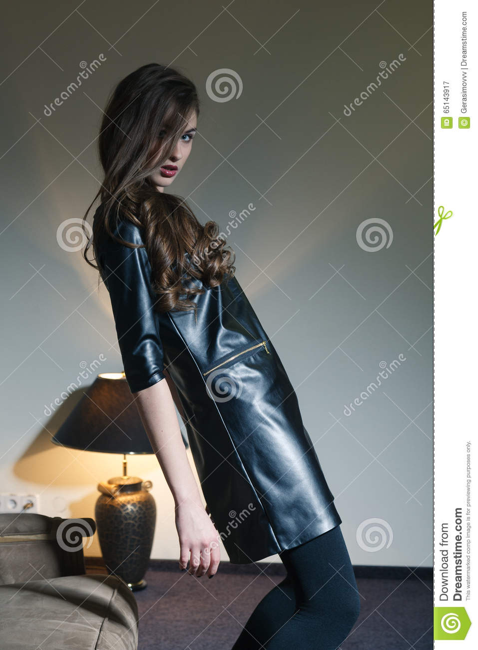 Young Seductive Woman In A Black Leather Dress Stock Photo