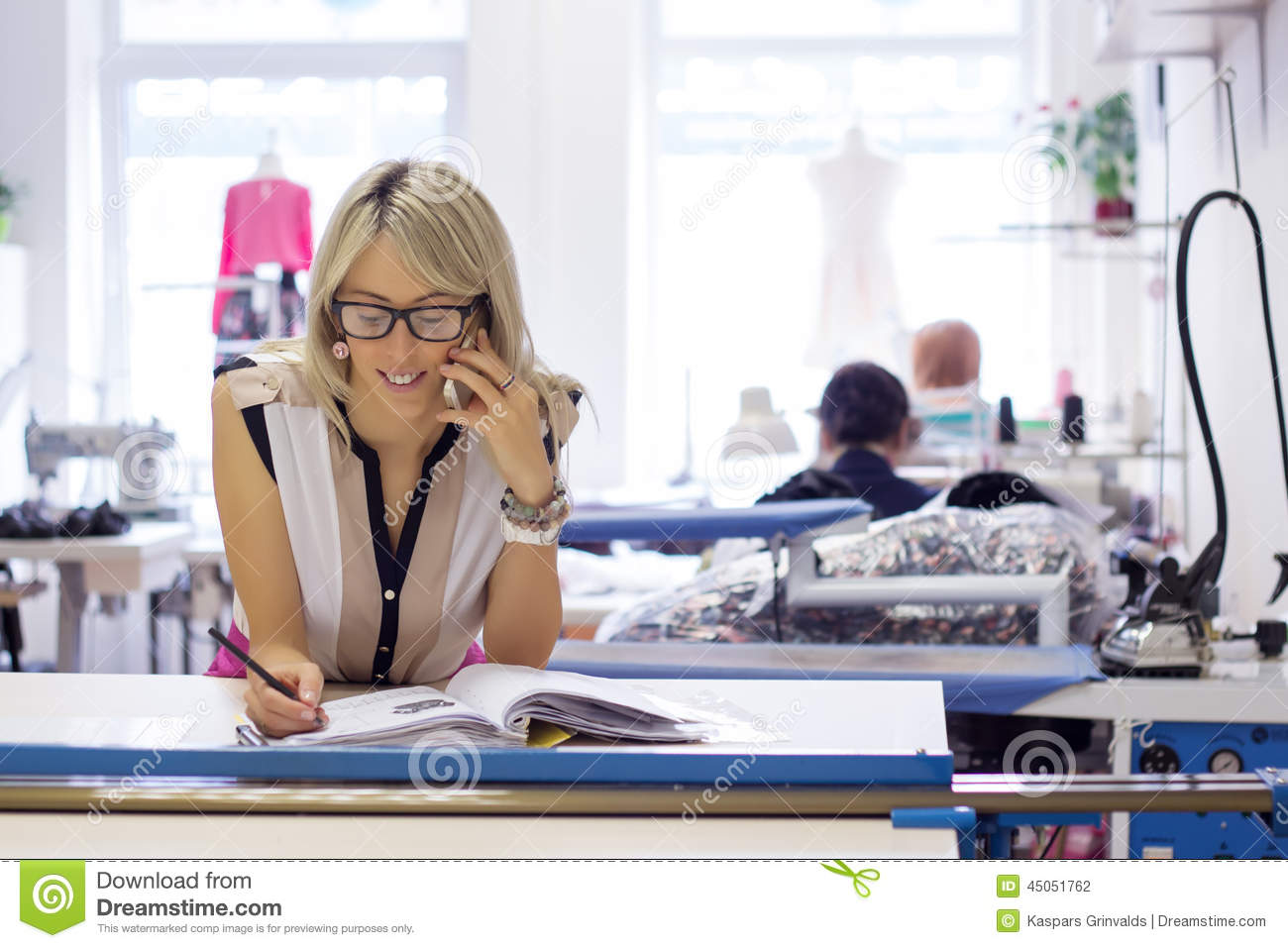Young self employed woman taking orders by phone