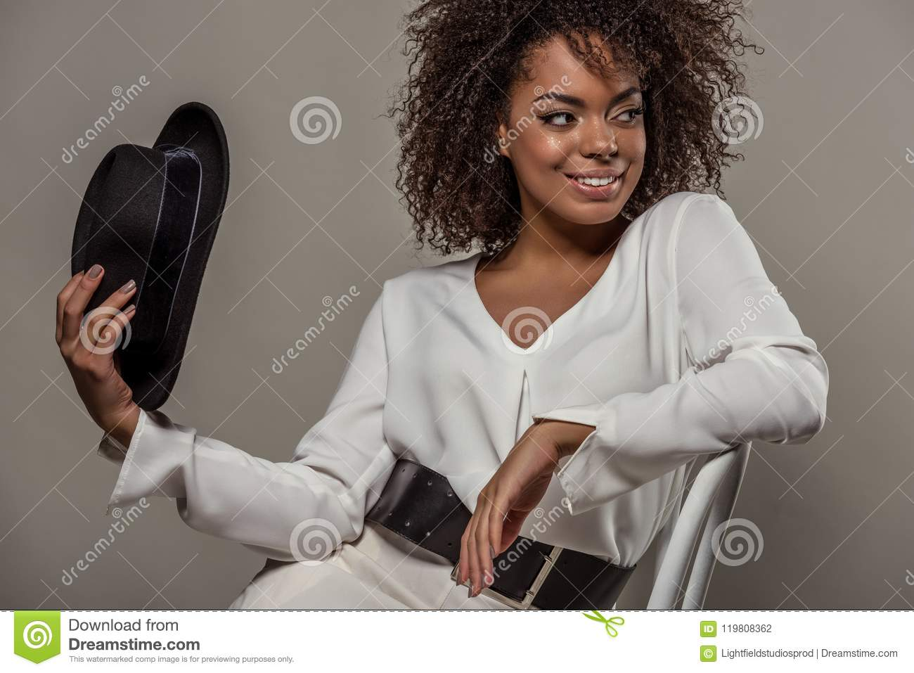 Young sensual african american woman in white shirt holding fedora hat
