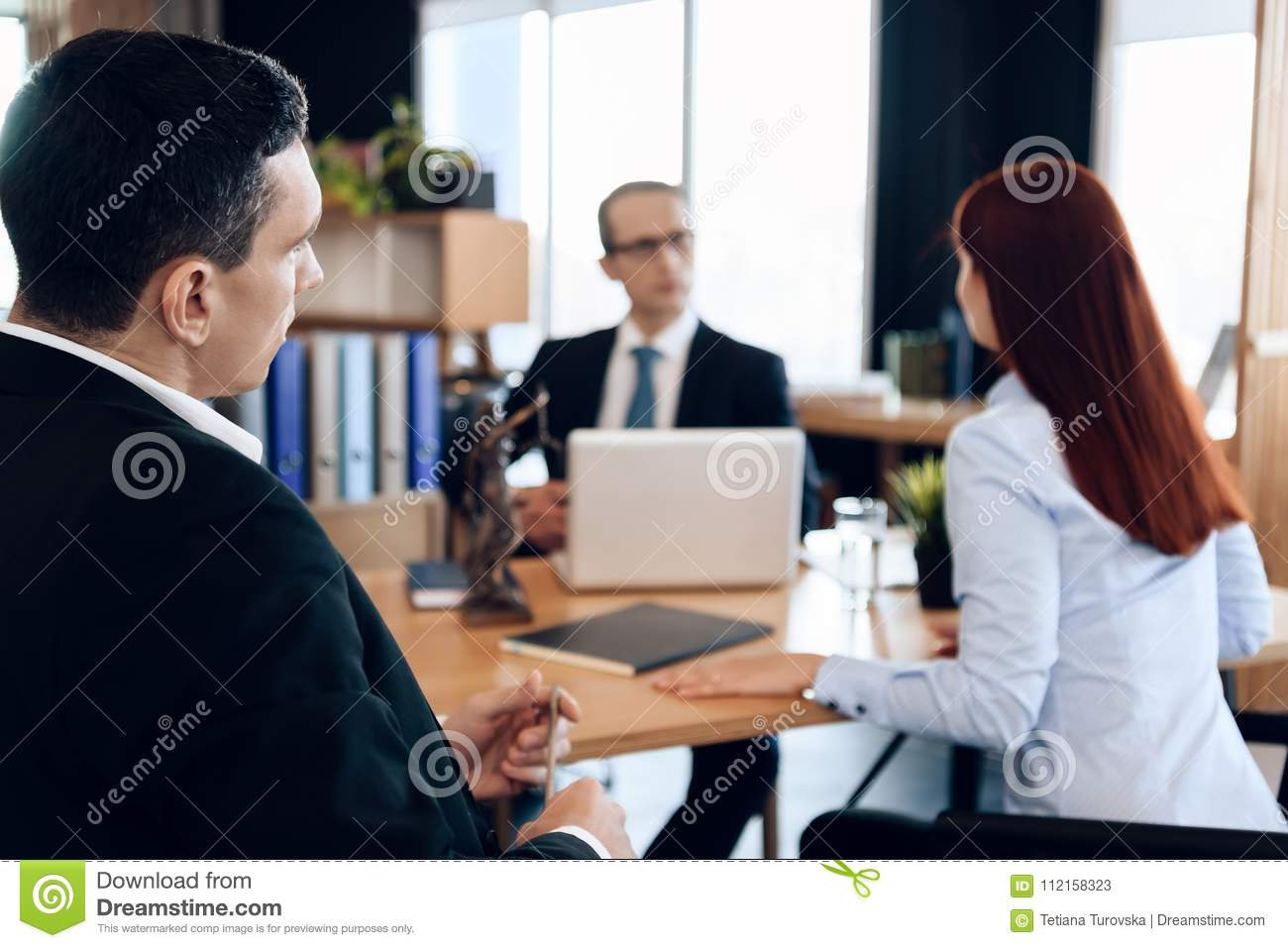Young serious couple consults, sitting in office of divorce advocate. Adult couple is divorced.