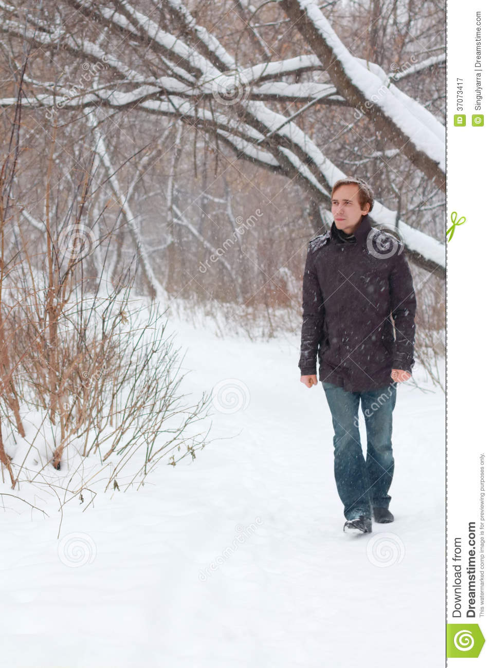 Young serious man in jeans walk in forest at winter