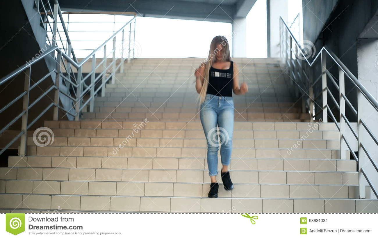 Young Blond Woman With Very Long Flowing Hair Goes Down The Stairs