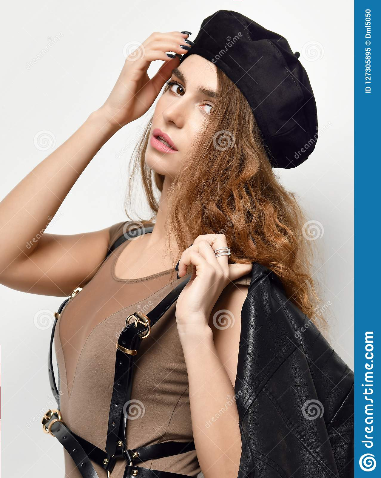 Young brunette woman in brown beret hat looking at the corner