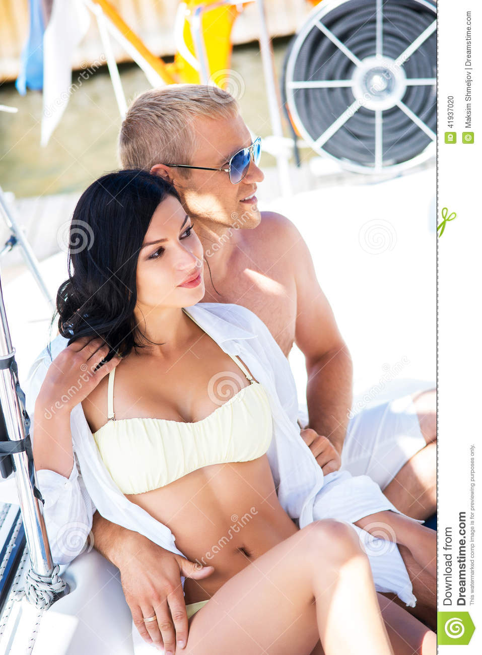 a02c7ed3c3 Handsome and rich men and a beautiful and women in swimsuit relaxing on a sailing  boat.