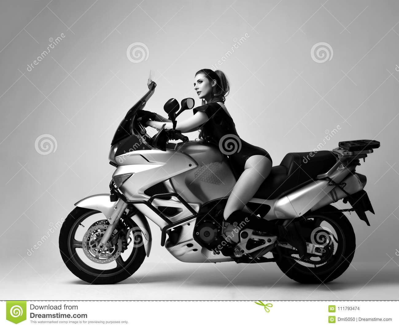 Young fashion woman sitting posing on motorcycle in studio