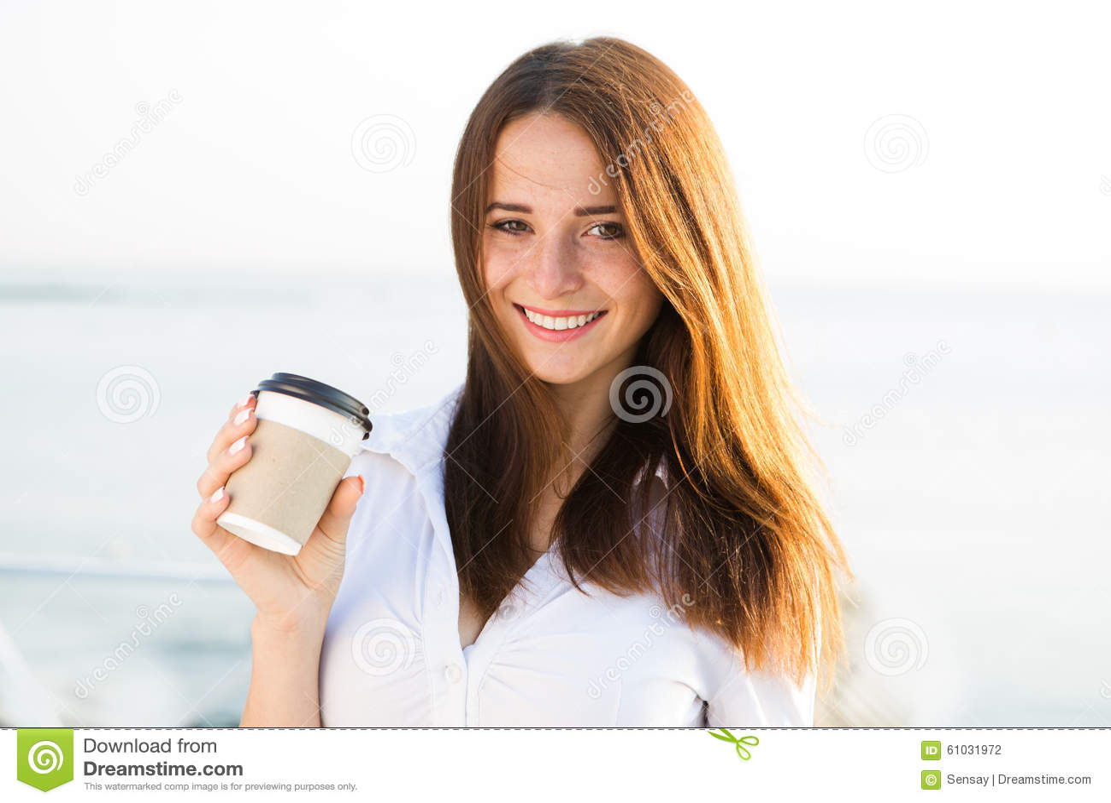 Young girl drinking coffee on seaside