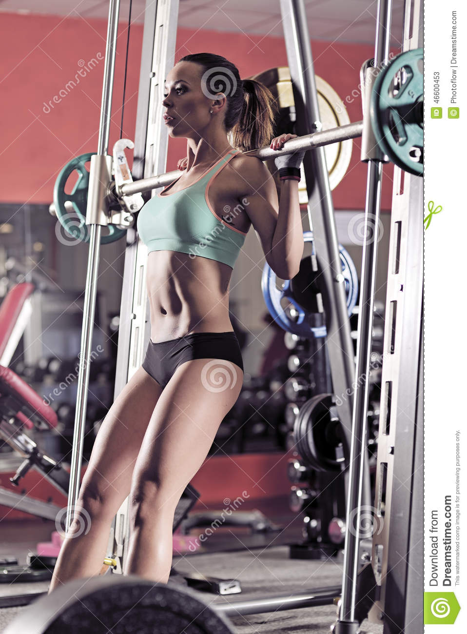 Young girl in the gym doing squat on red background